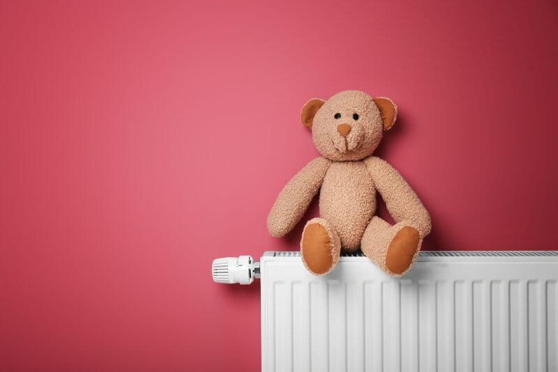 Teddy bear on heating radiator near pink wall